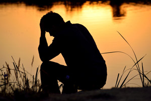 Photo of depressed man against sunset water background