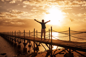 Sunset photo of man on pier with arms outstretched