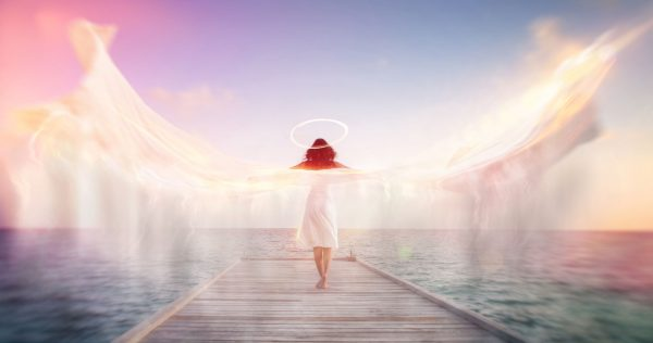 Sconceptual image of a female angel standing barefoot on an ocean jetty in a white dress with a halo and outspread wings showing motion blur with ethereal colorful sun flare effects