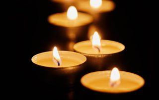 Burning votive candles on dark background - Jillian Frazin - Blessings of Jasmine