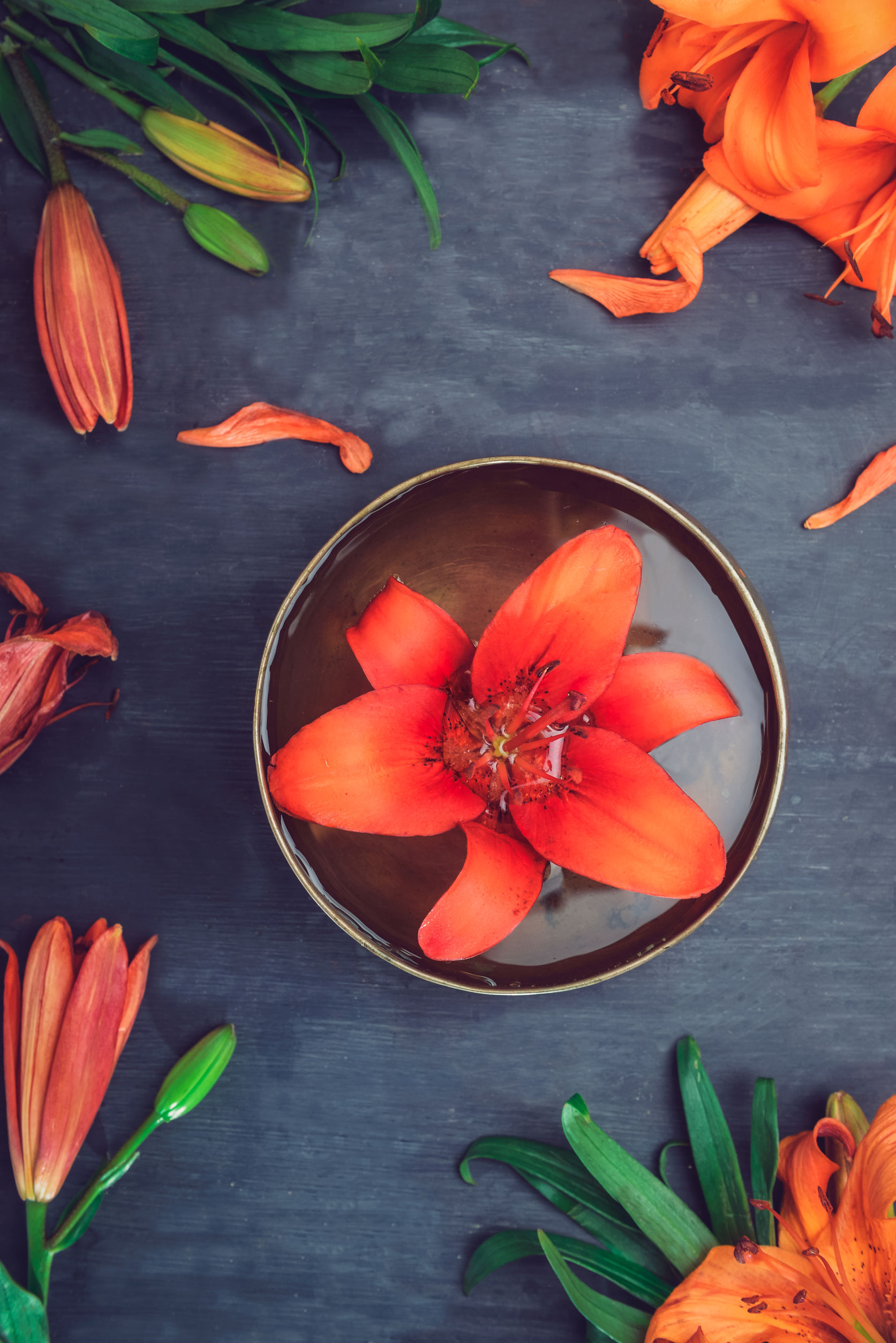 Tibetan singing bowl with floating lily inside. Burning candles, lily flowers and petals on the black wooden background. Meditation and Relax. Exotic massage, spa procedure. Selective focus